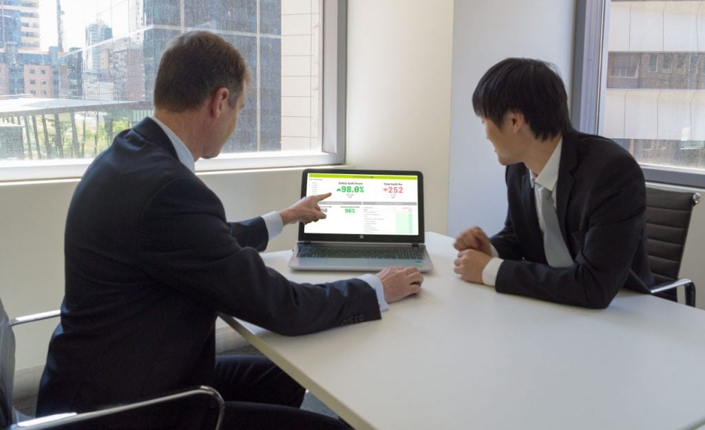 Photo of people sitting on front of laptop with Qlik