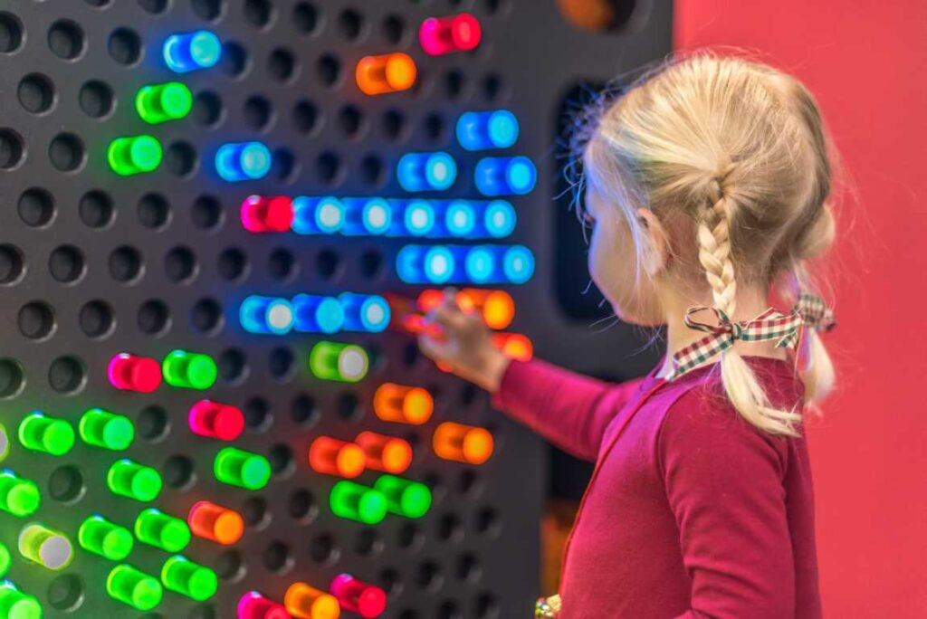 Little girl playing at light wall